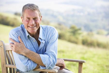 uomo felice: Senior uomo seduto all'aperto