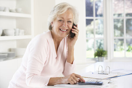 sorting out: Retired woman with household bills Stock Photo