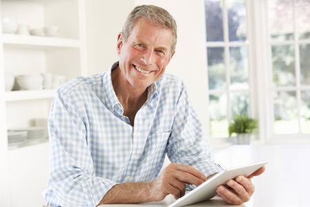 and the horizontal man: Senior man using tablet at home