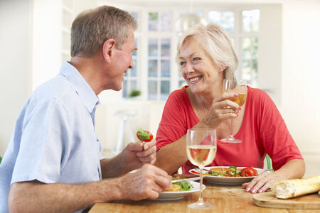 happily: Retired couple enjoying meal at home Stock Photo