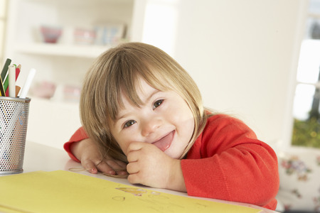 downs syndrome: Girl with Downs Syndrome drawing