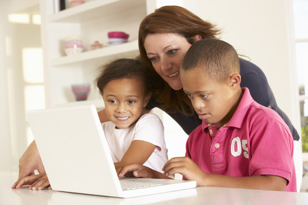 capable of learning: Mother and Downs Syndrome son with laptop