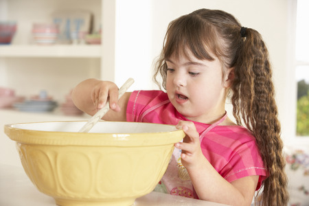 downs syndrome: Girl with Downs Syndrome baking Stock Photo