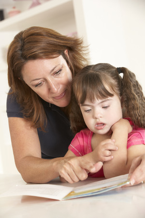capable of learning: Mother and Downs Syndrome girl reading Stock Photo