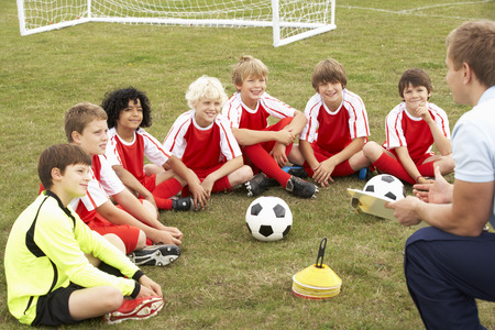 Junior voetbalteam training met coach Stockfoto