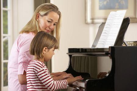 tocando piano: Chica joven que toca el piano en clase de música
