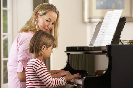 teaching music: Young girl playing piano in music lesson