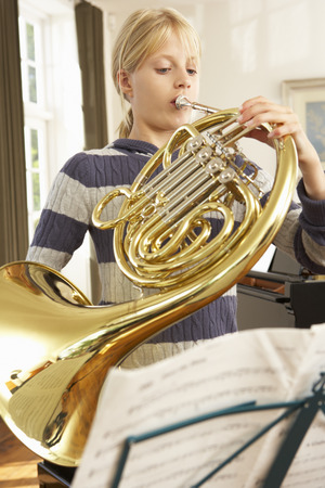 french ethnicity: Girl playing French horn at home