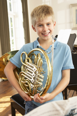 french ethnicity: Boy holding French horn at home
