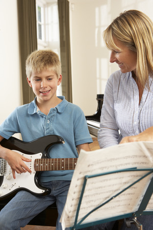 teaching music: Boy playing electric guitar in music lesson