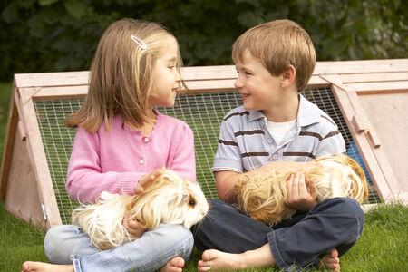 cavie: Giovane ragazzo e ragazza in possesso di giardino cavie Archivio Fotografico