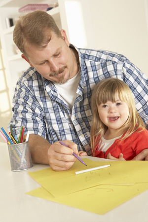 down's syndrome: Father and Downs Syndrome daughter drawing Stock Photo