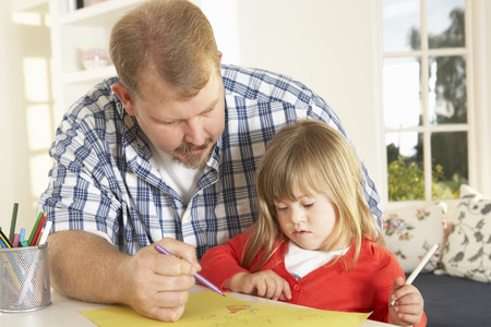 downs syndrome: Father and Downs Syndrome daughter drawing Stock Photo