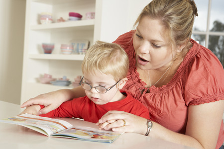 Mother and Downs Syndrome son reading