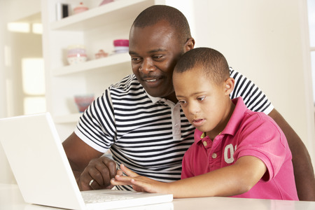 Father and Downs Syndrome son with laptop Stock Photo