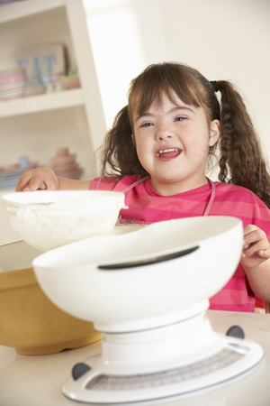capable of learning: Girl with Downs Syndrome baking Stock Photo