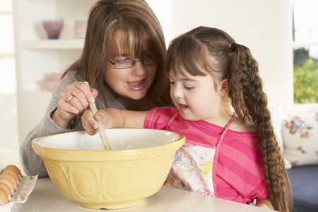 downs syndrome: Girl with Downs Syndrome baking with mother Stock Photo