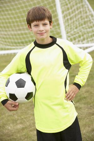arquero futbol: Retrato del niño en el kit de portero con el balón Foto de archivo