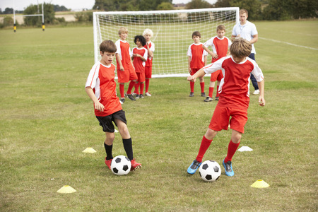 Junior football team training with coach