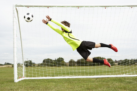 fitness goal: Boy goalkeeper jumping to save goal