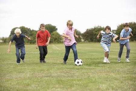 jugando futbol: Muchachos que juegan con el fútbol en el parque Foto de archivo