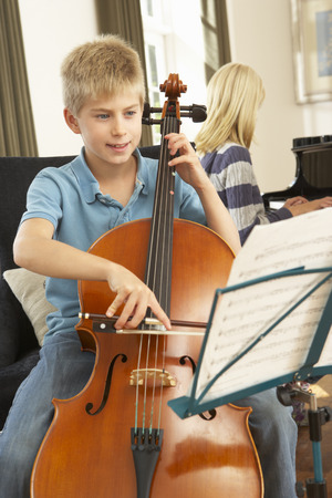 wallingford: Boy and girl playing cello and  piano at home Stock Photo