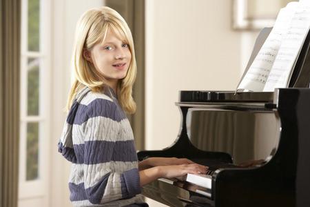 tocando piano: Muchacha que toca piano de cola en el hogar Foto de archivo