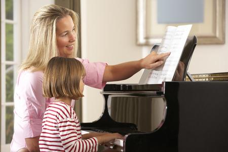 Jong meisje speelt piano in muziekles