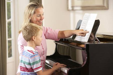 Junger Junge im Unterricht mit Klavierlehrer