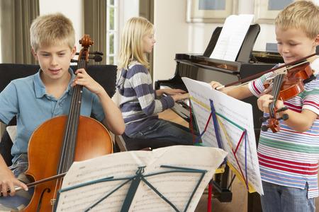 hermanos jugando: Los ni�os tocando instrumentos musicales en casa Foto de archivo