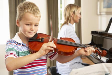 tocando piano: El muchacho joven que toca el violín acompañado por el maestro Foto de archivo