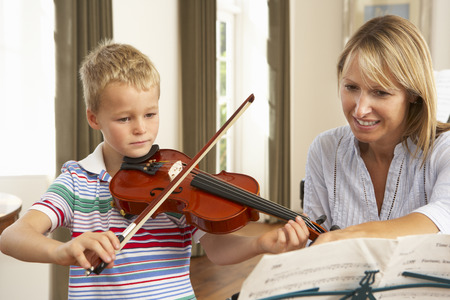 violin: Young boy playing violin in music lesson Stock Photo