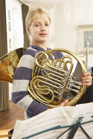 french ethnicity: Girl holding French horn at home