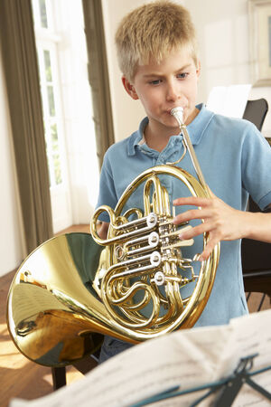 french horn: Boy playing French horn at home