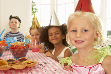 Young children eating at birthday party photo