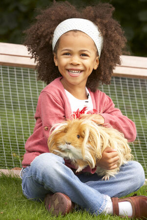 wallingford: Young girl in garden holding guinea pig
