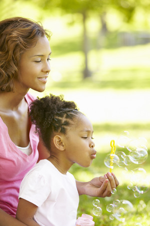blowing bubbles: Mother and daughter blowing bubbles
