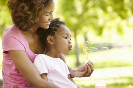 Moeder en dochter om bellen te blazen Stockfoto