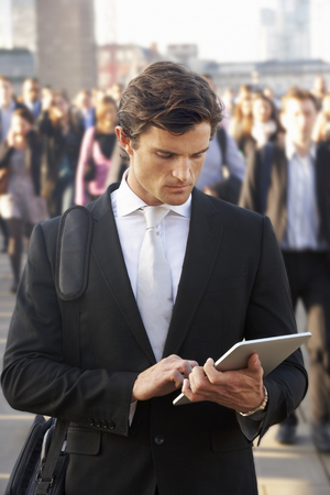 incidental people: Male commuter in crowd using tablet