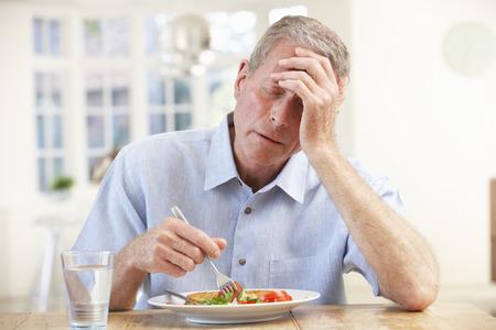 Zieke oudere man proberen te eten Stockfoto