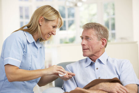 treating: Senior man visited at home by nurse Stock Photo