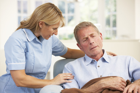 Senior man visited at home by nurse Stock Photo