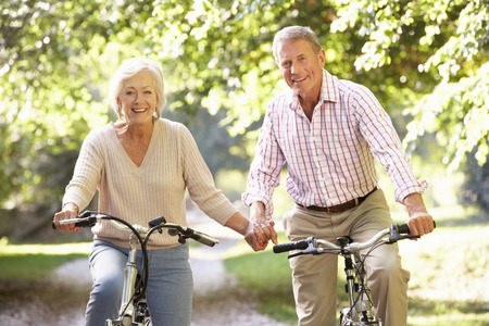 fits in: Senior couple cycling in park
