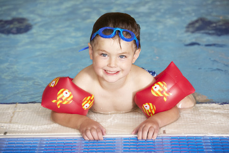 floats: Young boy in swimming pool
