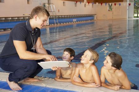 Boys having swimming lesson Imagens
