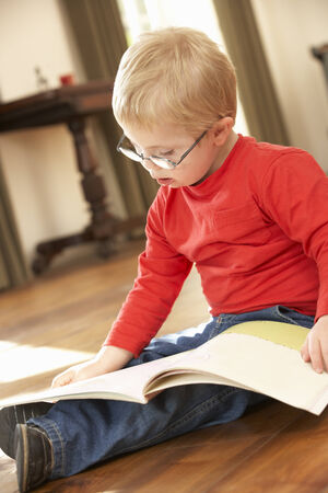 4 year old: 4 year old boy with Downs Syndrome reading Stock Photo