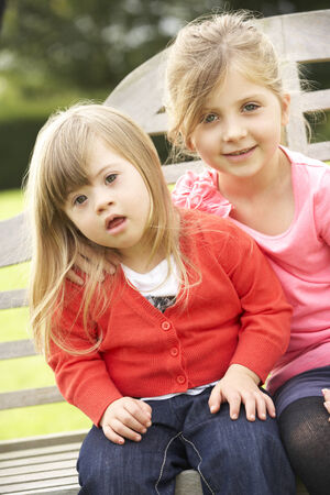 downs syndrome: Girl with younger Downs Syndrome sister Stock Photo