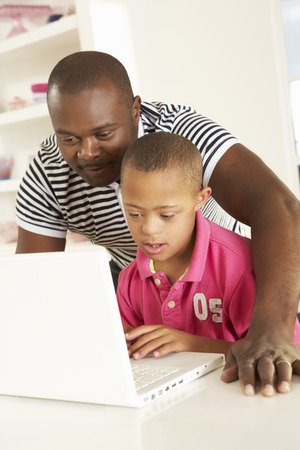 downs syndrome: Father and Downs Syndrome son with laptop Stock Photo