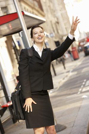 hailing: Businesswoman hailing bus at stop