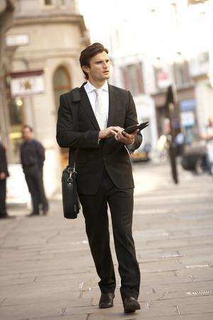 incidental people: Businessman with tablet walking down street